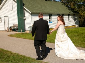 The bride and groom walking away after at an outdoor Wisconsin wedding ceremony in River Falls WI.